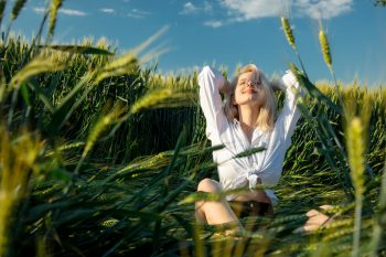 beautiful blonde girl in a white shirt sits between wheat ears in field during sunset